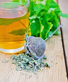 Herbal tea with mint in a mug and strainer — Stock Photo