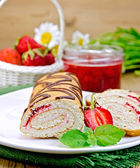 Roulade with strawberries and daisies on a board — Stock Photo