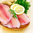 Fillets tilapia in pottery on the board — Stock Photo #40952241