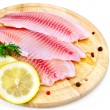 Stock Photo: Fillets tilapia with lemon and dill on a board