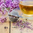 Herbal tea from oregano with strainer on board — Stock Photo #40952459