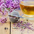 Herbal tea from oregano with strainer on board — Stock Photo
