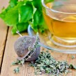 Stock Photo: Herbal tefrom melissin cup with strainer on board