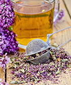 Herbal tea from oregano with strainer in glass mug — Stockfoto