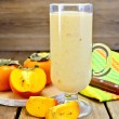 Milkshake with persimmons in goblet on board — Stock Photo #41258427