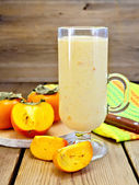 Milkshake with persimmons in goblet on board — Stock Photo