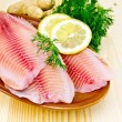 Fillets tilapia in pottery on the board — Stock Photo #41653719