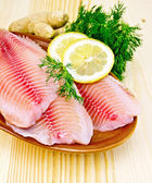 Fillets tilapia in pottery on the board — Stock Photo