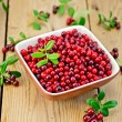 Lingonberry ripe in bowl on board — Stock Photo