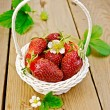 Strawberries in basket with flowers on board — Stock Photo