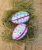 Easter eggs with ribbons and sequins on board — Stock Photo