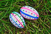 Easter eggs with ribbons and sequins on grass — Stock Photo