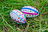 Easter eggs with ribbons and stars on grass — Stockfoto