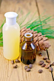 Oil and lotion with cedar cone on board — Stock Photo