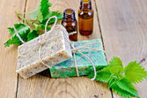Soap homemade and oil with nettle on board — Stock Photo