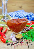 Adjika in glass gravy boat on board with oil — Stock Photo