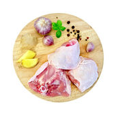 Chicken thigh cut on round board — Stock Photo