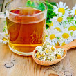 Herbal chamomile tea in spoon with mug on board — Stock Photo