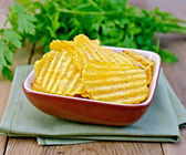Chips grooved in bowl on board — Stock Photo