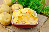Chips in bowl with potatoes on sacking and board — Stock Photo