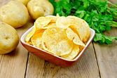 Chips in clay bowl with potatoes on board — Stock Photo