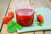 Jam of strawberry with berries and leaf on board — Stock Photo