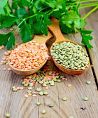 Lentils red and green in spoons with parsley on board — Stock Photo