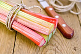 Rhubarb with twine and knife on board — Stockfoto