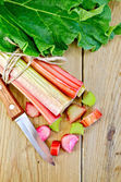 Rhubarb cut with leaf on a wooden board — Stock Photo
