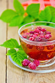 Tea with raspberries in glass cup and napkin on board — Stock Photo