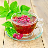 Tea with raspberries in glass cup on board — Stockfoto