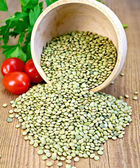 Lentils green in bowl with tomatoes on board — Stock Photo