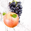 Juicy red apple and bunch of grapes in water splash isolated on — Stock Photo
