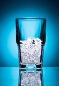 Vaso vacío con hielo aislado sobre un fondo azul — Foto de Stock
