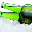 Close-up Two green bottles of beer with condensation cool in ice — Stock Photo #28059973