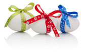 Three Easter eggs with festive bow isolated on white background — Foto Stock