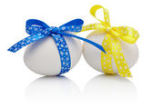 Two Easter eggs with festive blue and yellow bow isolated on whi — Stock Photo