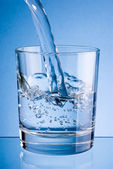 Pouring water into glass on a blue background — Stock Photo