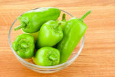 Green peppers in transparent glass bowl on wooden board — Stockfoto