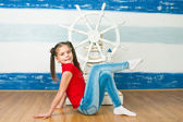 Girl in a red T-shirt against a ship steering wheel — Stock Photo