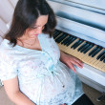 The pregnant woman near a piano — Stock Photo #13742944