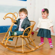 Little girl on a horse rocking chair — Stock Photo #16792061
