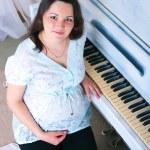 The pregnant woman near a piano — Stock Photo #19627733