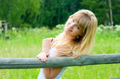 The girl stands near a fence — Stock Photo
