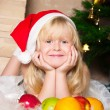 The girl under the Christmas fir-tree — Stockfoto