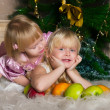 The girls under the Christmas fir-tree — Stock Photo