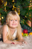 The girl under the Christmas fir-tree — Stock Photo