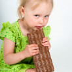 Young girl eating bar of chocolate — Stock Photo #23399872