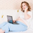 The pregnant woman with the laptop and a mobile phone on a sofa — Stock Photo #3662272