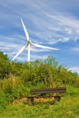 Bench and wind turbine generating electricity — Stock Photo